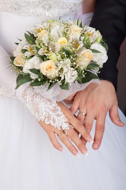 Braut- und bräutigamhände mit eheringen und blumenstrauß von rosen Premium Fotos