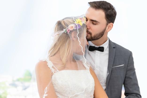 Braut- und bräutigampaare des kaukasischen kusses und der umarmung im hochzeitsstudio. Premium Fotos