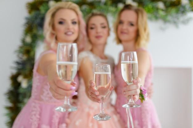 Braut und brautjungfern feiern hochzeitstag und trinken zusammen rosa champagner aus gläsern Premium Fotos