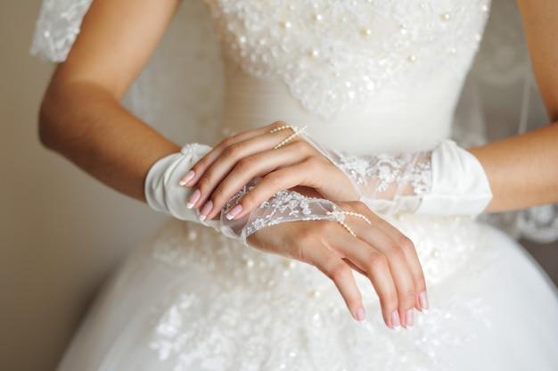 Brauthände auf hochzeitskleid Premium Fotos