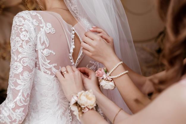 Brautjungfer, die brautkorsett hilft und ihr kleid erhält Premium Fotos