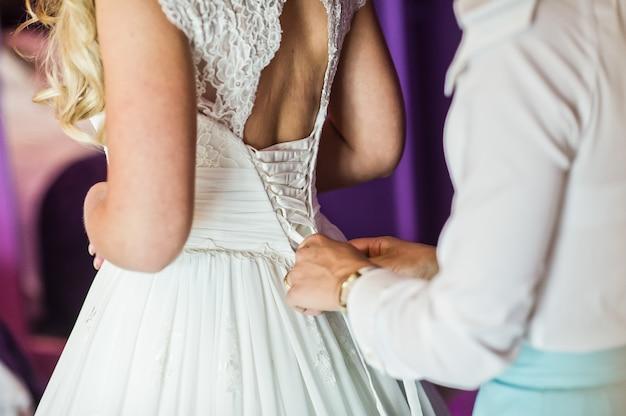 Brautjungfer hilft, das brauthochzeitskleid, hotelinnenraum, purpurroter hintergrund anzukleiden Premium Fotos