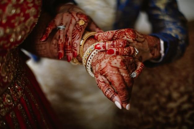 Brautjungfer hilft der indischen braut, schmuck auf ihre hand zu setzen Kostenlose Fotos
