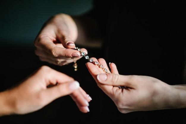 Brautjungfer hilft, ein armband für die braut an seinen arm zu legen. braut zieht schmuck an, konzentriert sich auf armband. brautvorbereitung für die hochzeitszeremonie. Premium Fotos