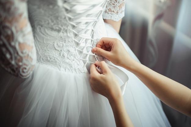 Brautjungfer macht bogenknoten auf dem rücken des hochzeitskleides der bräute Kostenlose Fotos