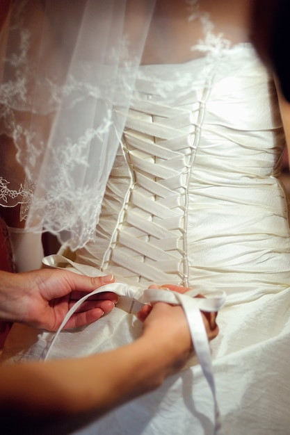 Brautjungfern helfen der braut, ein hochzeitskleid zu tragen. Premium Fotos