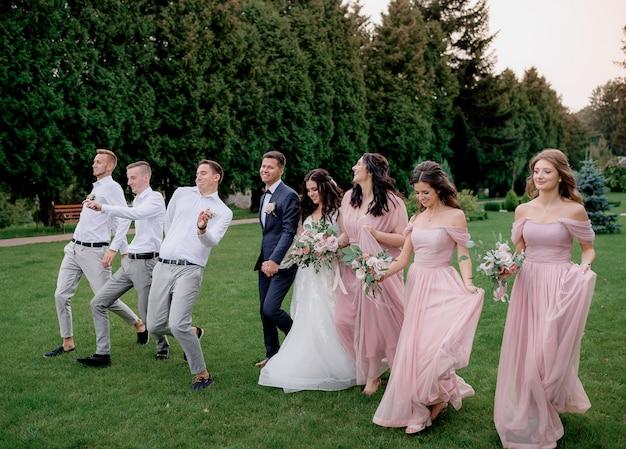 Brautjungfern in rosa kleidern, beste männer und hochzeitspaare gehen glücklich auf dem grünen hof spazieren Kostenlose Fotos