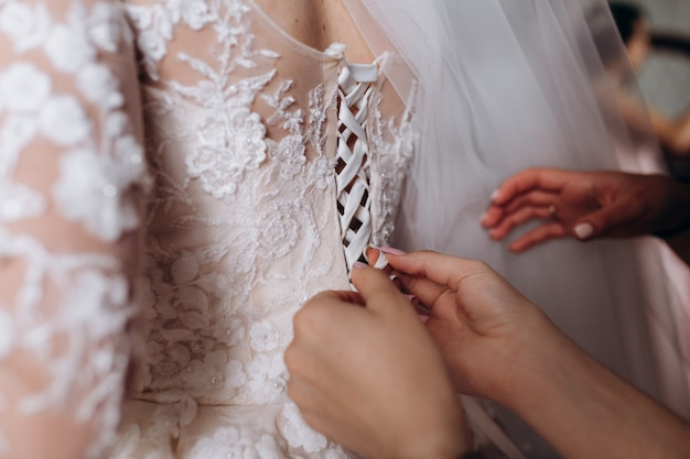 Brautjungfernhände binden das hochzeitskleidkorsett Kostenlose Fotos