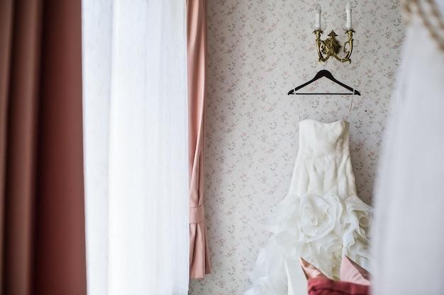 Brautkleid auf einem kleiderbügel im eleganten interieur des hotels Premium Fotos