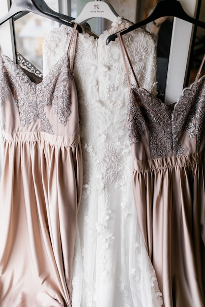 Brautkleid und ihre beiden brautjungfernkleider hängen an kleiderbügeln Kostenlose Fotos