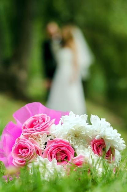Brautstrauß auf unscharfem schattenbild einer braut mit dem bräutigam Premium Fotos