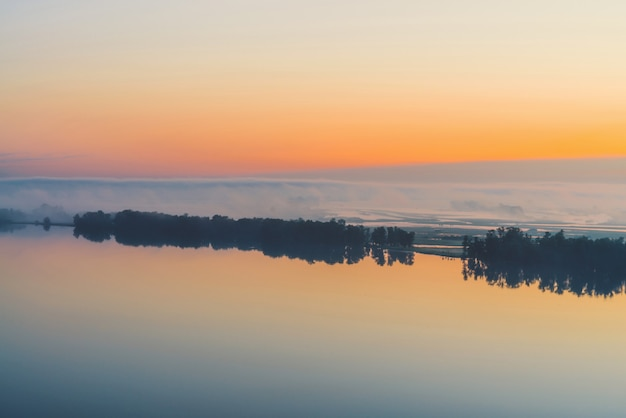 Breiter mystischer fluss fließt entlang diagonales ufer mit schattenbild der bäume und des starken nebels. goldglühen im himmel vor dem morgengrauen. ruhiger morgen stimmungsvolle landschaft von majestätischer natur in warmen tönen. Premium Fotos