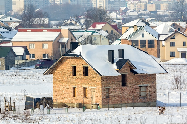 Breites winterpanorama des ländlichen landes für entwicklung im ruhigen wohnvorstadtgebiet. neues nicht fertiges backsteinhaus von entfernten dorf- und hochstadtgebäuden unter blauem himmel. Premium Fotos