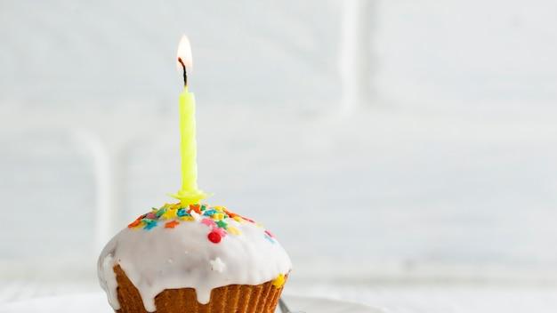 Brennende kerze auf cupcake mit weißer glasur Kostenlose Fotos