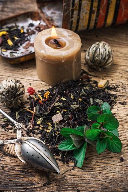 Brennende kerze auf dem hintergrund des zerstreuten tees mit kalk und minze in der rustikalen art. Premium Fotos
