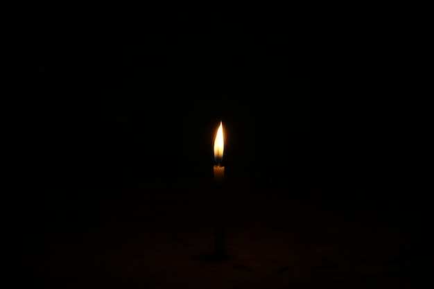 Brennende kerze auf einem dunklen hintergrund Kostenlose Fotos