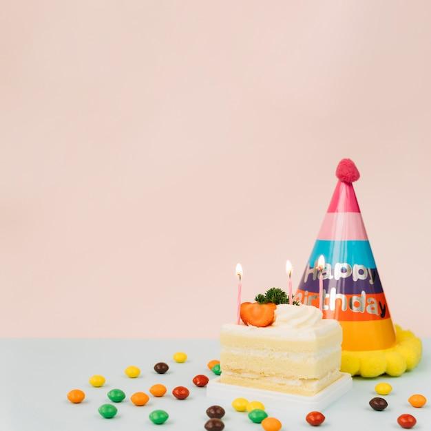 Brennende kerzen auf kuchen; süßigkeiten und geburtstagshut gegen farbigen hintergrund Kostenlose Fotos
