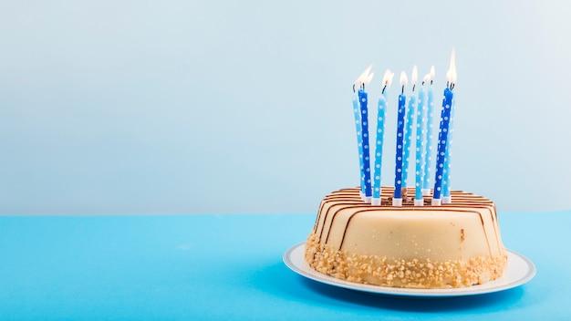 Brennende Kerzen über dem köstlichen Kuchen gegen blauen Hintergrund Kostenlose Fotos
