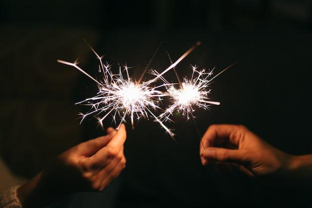 Brennende neujahrswunderkerze. bengalisches licht, das in kleine glitzer streut. Premium Fotos