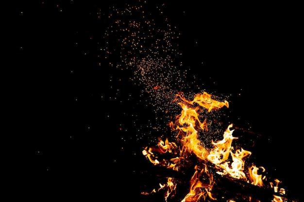 Brennende wälder mit feuerfunken, flammen und rauch. seltsame seltsame seltsame elementare feurige figuren in der schwarzen nacht. kohle und asche. abstrakte formen in der nacht. lagerfeuer im freien auf natur. Premium Fotos
