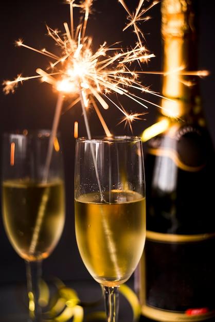 Brennende wunderkerze im champagnerglas auf dunklem hintergrund Kostenlose Fotos
