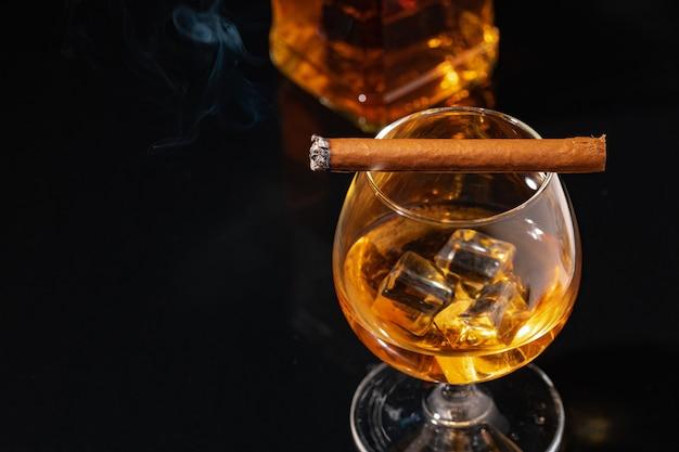 Brennende zigarre und glas whisky auf schwarzer nahaufnahme Premium Fotos