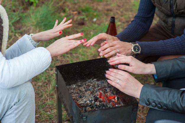 Brennendes holz im grill und rote kohlen mit dem strom, der von ihm aufkommt. kleiner junge im roten mantel wärmt seine gefrorenen hände über den flammen der grillpfanne. picknick im winter Premium Fotos
