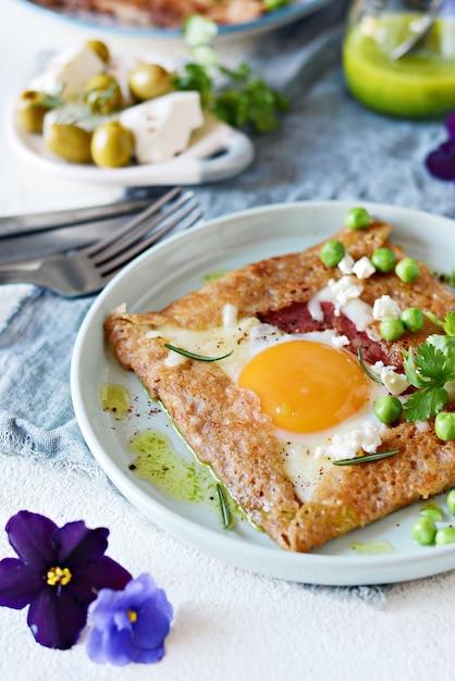 Bretonischer traditioneller pfannkuchen aus buchweizenmehl mit schinken, käse, ei, feta, erbsen und grüner butter. Premium Fotos