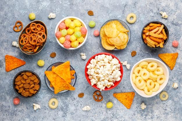 Brezeln, pommes, cracker und popcorn in schalen Kostenlose Fotos