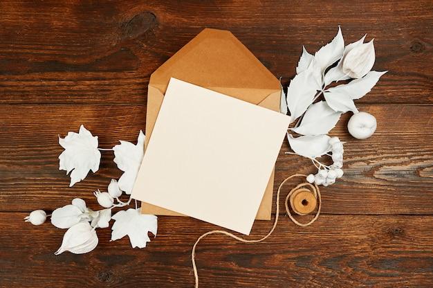 Brief blankopapier in grünen umschlag mit hölzernen schneeflocken und geschenkboxen auf holztisch Premium Fotos