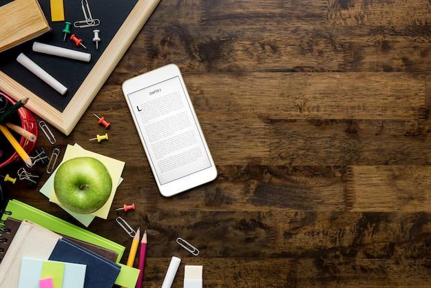 Briefpapier- und bildungsversorgungen, die ebook-leser auf hölzernem hintergrund einschleichen Premium Fotos