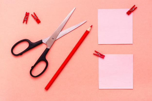 Briefpapierblätter für die anmerkungen befestigt, bleistift und scheren auf roter draufsicht Premium Fotos