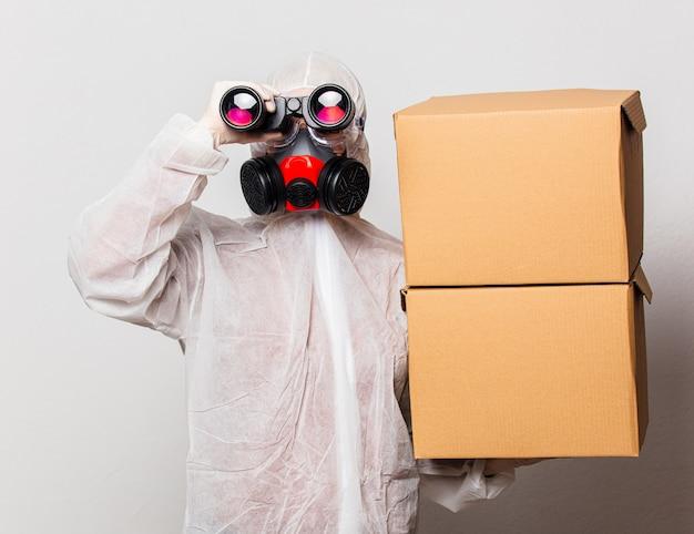 Briefträgerin im schutzanzug und brille mit maske hält lieferboxen und fernglas Premium Fotos
