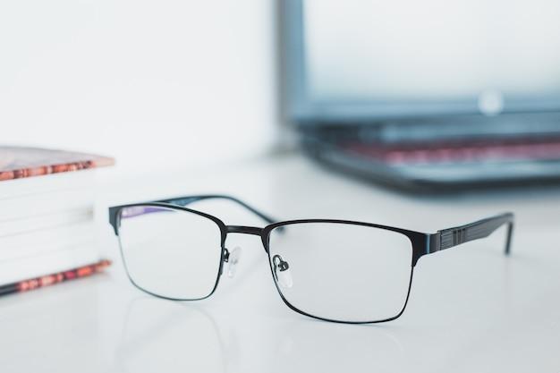 Brille mit buch und laptop Premium Fotos