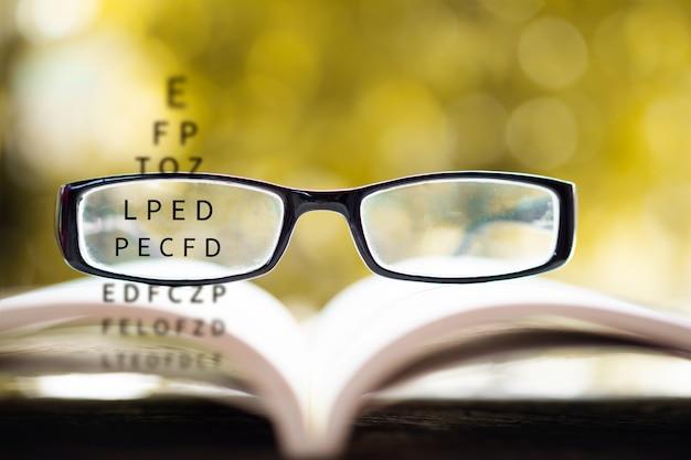 Brillen auf buch mit sehtestkarte Premium Fotos