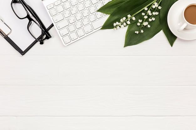 Brillen, klemmbrett, tastatur, blume und blätter mit kaffeetasse auf schreibtisch Kostenlose Fotos