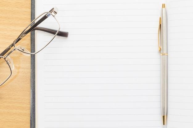 Brillen und stift auf notizblock mit leerseite Premium Fotos