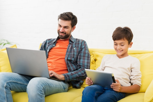 Bringen sie das arbeiten an dem laptop und sohn hervor, die auf tablette schauen Kostenlose Fotos