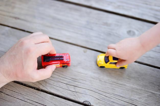 Bringen sie mit seinem kleinen sohn hervor, der mit spielzeugautos spielt Premium Fotos
