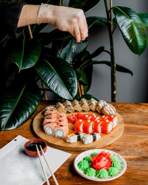 Brötchen aus fisch auf der runden holzoberfläche zusammen mit stöcken und schwarzer sauce auf der grauen oberfläche Kostenlose Fotos
