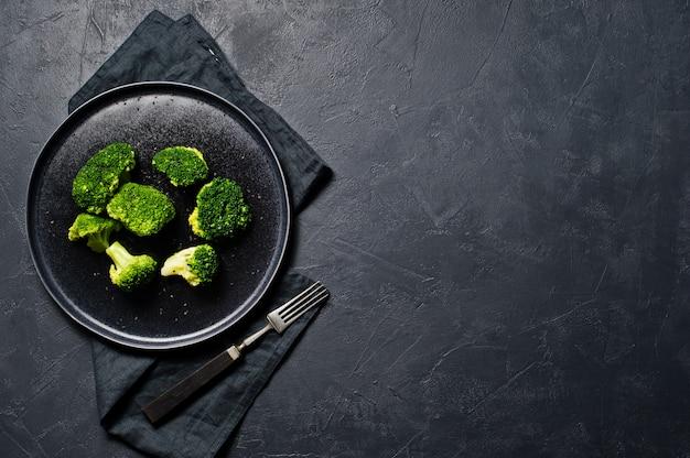 Brokkoli auf einem schwarzen teller. Premium Fotos