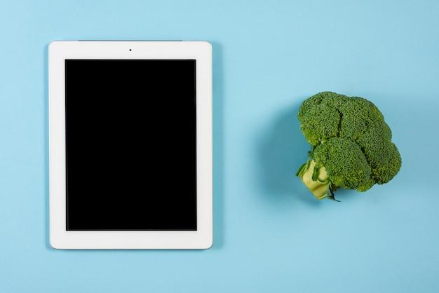 Brokkoli nahe der digitalen tablette mit schwarzer bildschirmanzeige auf blauem hintergrund Kostenlose Fotos