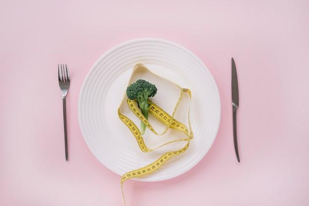 Brokkoli und maßband auf einem teller Kostenlose Fotos