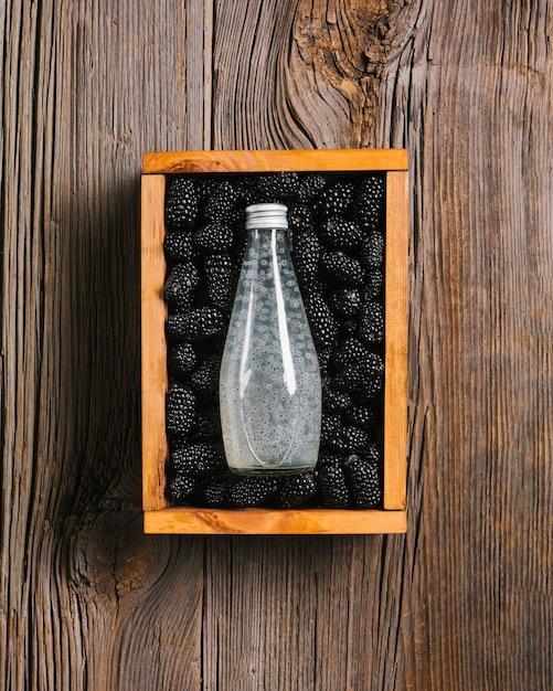 Brombeersaftflasche auf hölzernem hintergrund Kostenlose Fotos