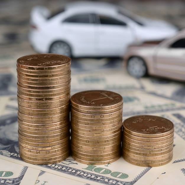Bronzemünzen häufen mit unscharfen spielzeugautos im hintergrund an Premium Fotos