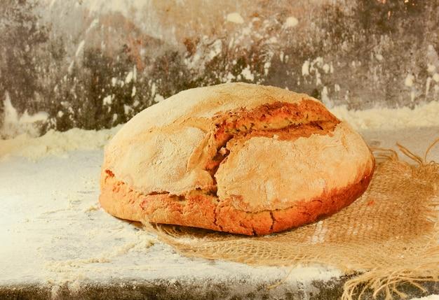 Brot auf dem tisch. detail des frischen traditionsgemäß gebackenen brotes. brot auf dunkel. bäckerei, konzept kochend. Premium Fotos