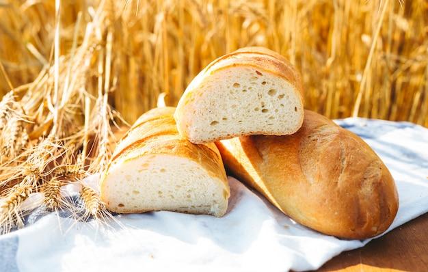 Brot auf dem tisch und weizen auf dem gebiet des weizens und des sonnigen tages Premium Fotos