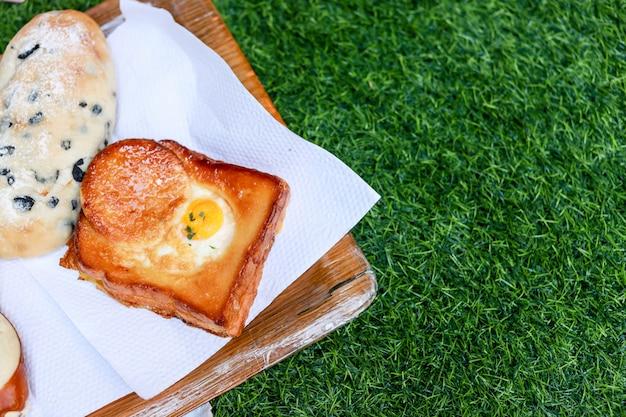 Brot auf hölzerner platte und grünem gras Premium Fotos