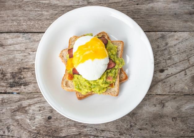 Brot, avocadosoße, speck, spinat, ei benedict auf weißer platte und alter hölzerner hintergrund Premium Fotos