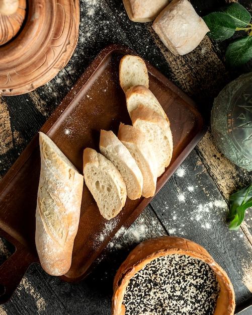 Brot baguette an bord mit sesam und brötchen auf dem tisch Kostenlose Fotos